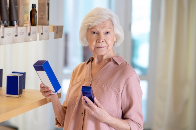 향료 제조업. 부티크에서 향수를 선택하는 회색 머리 여자