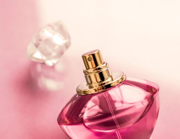 光沢のある背景に香水スパとブランディングコンセプトのピンクの香水瓶甘い花の香りの魅力的な香りとホリデーギフトと高級美容化粧品のブランドデザインとしてのオードパルファム