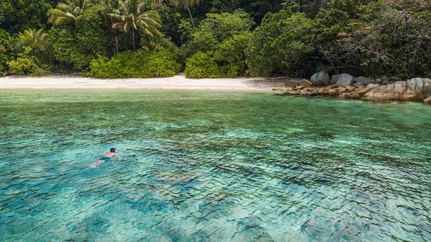 Perhentian島の砂浜とジャングルの近くの熱帯の海でシュノーケリングの男。アジアの休日旅行先。