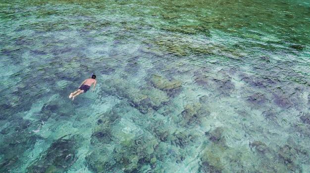 クリスタルの青緑色の水とperhentian島の近くのサンゴ礁でシュノーケリング白人観光客の空撮。