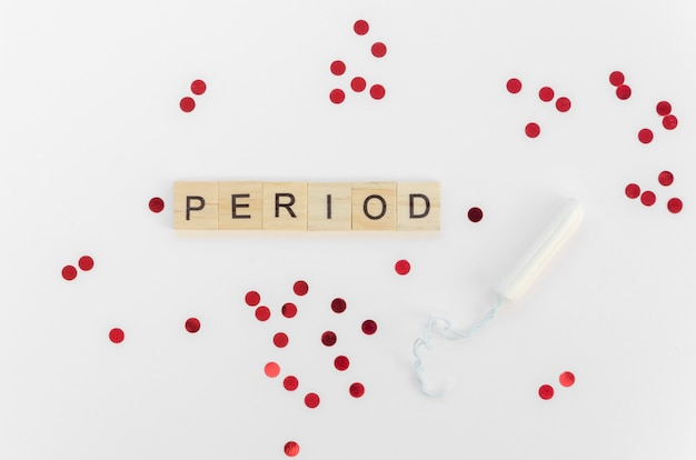 Period word with scrabble letters and red sequins