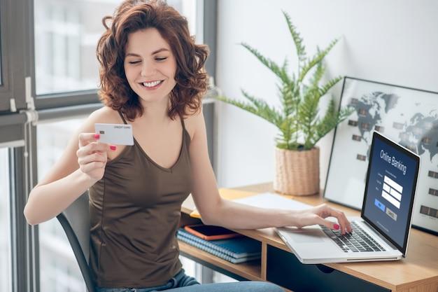 定期的な支払い。クレジットカードを持ってオンラインで支払いを計画しているきれいな女性