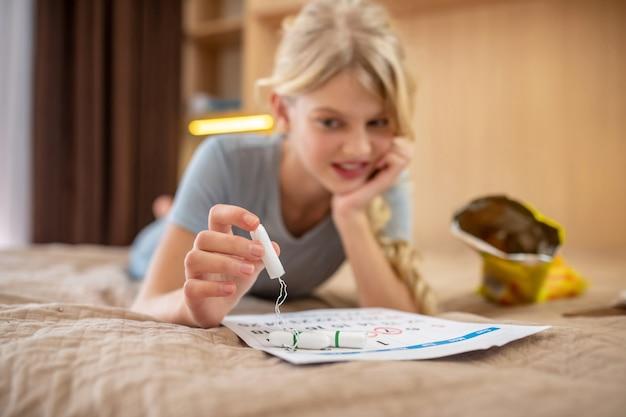 Календарь периодов. юная блондинка отмечает дни менструации в календаре