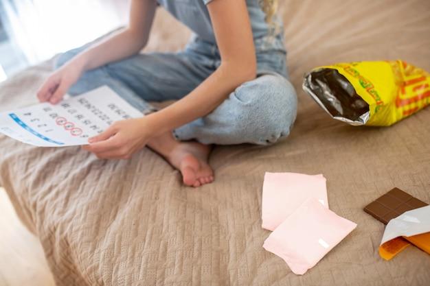 Periods calendar. a blonde teen ,marking days of her periods in a calendar