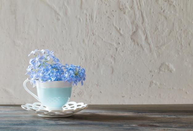 木製のテーブルの上のカップのツルニチニチソウ