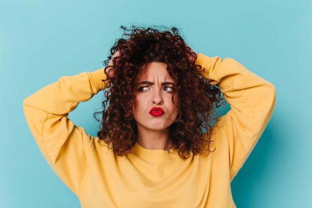 Ragazza vivace scompiglia i capelli ricci con un'espressione facciale divertente. colpo di donna con labbra rosse sullo spazio blu.