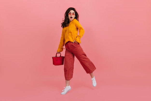 Perky girl in stylish glasses stares in amazement, walking on pink wall. brunette in culottes and orange blouse posing with red handbag.