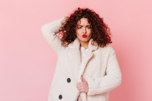 Веселая девушка с красными губами трогает волосы и делает забавное выражение лица. женщина в белом халате позирует на розовом пространстве.