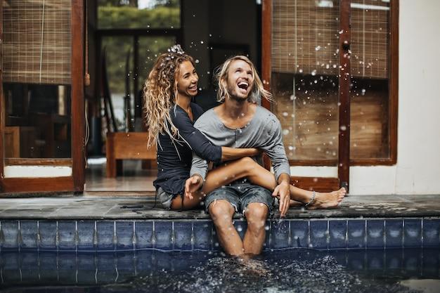 Веселый мужчина и его девушка обнимаются, смеются и плещут воду