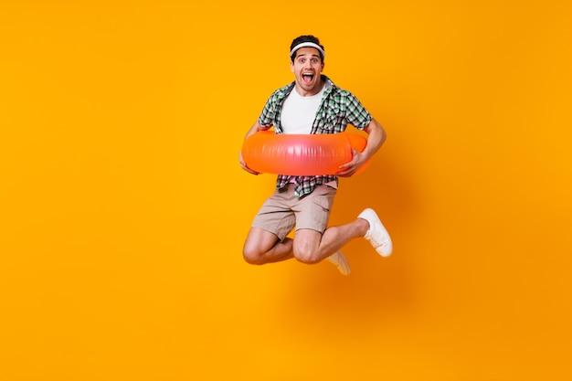 Веселый мужчина в шортах и рубашке надевает надувной круг и прыгает по оранжевому пространству.