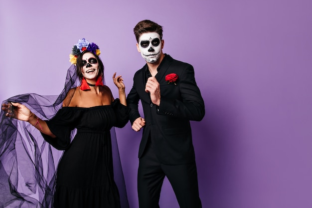 Perky men and his woman in black outfits have fun and dance at halloween party.