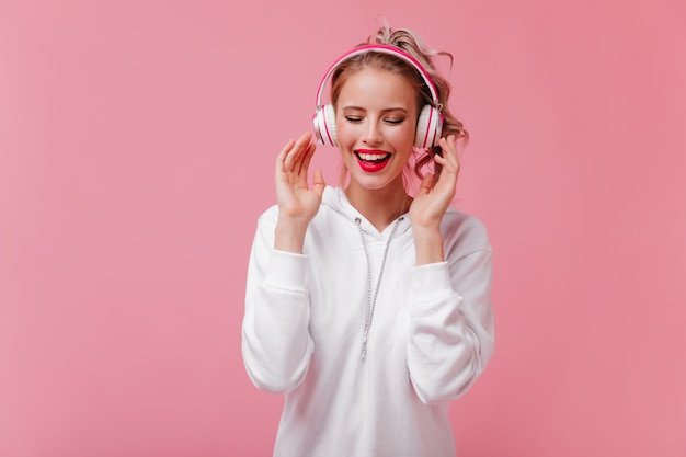 Perky woman in big headphones loves to listen to music