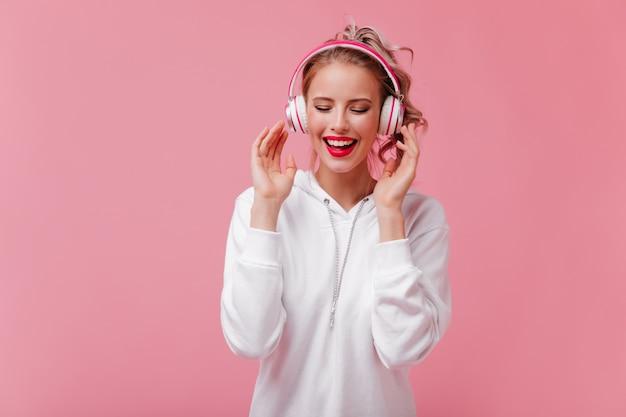 大きなヘッドフォンで元気な女性は音楽を聴くのが大好き