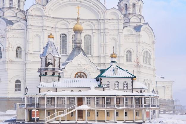 Пермский край, россия - 21 декабря 2020 года: макет старой церкви на фоне настоящего храма белогорского монастыря в туманный зимний день