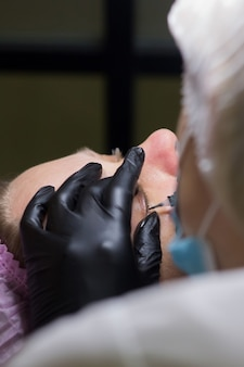 Permanent eye makeup between eyelashes microblading permanent makeup on eyes in a beauty salon