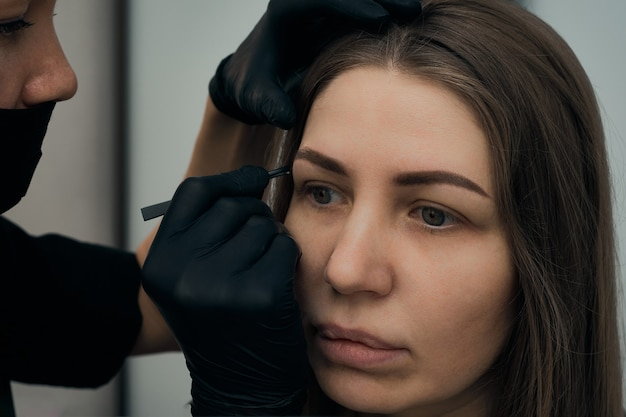 Permanent eyebrow makeup procedure eyebrow tattooing process the use of tools by a master for permanent eyebrow makeup