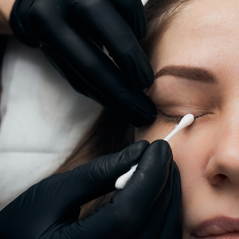 Permanent eyebrow makeup procedure. eyebrow tattooing, process. the use of tools by a master for permanent eyebrow makeup.
