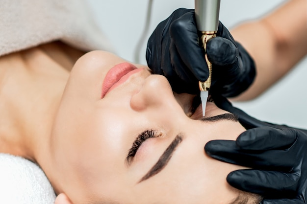 Permanent make up on eyebrows by professional cosmetologist.