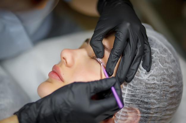 Permanent make up eyeliner procedure, applying on young girl