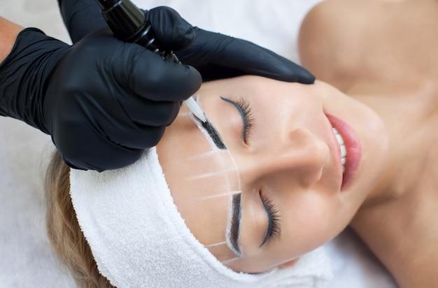 Перманентный макияж бровей красивой женщины с густыми бровями в салоне красоты