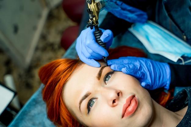 ビューティーサロンの眉毛にアートメイクとタトゥーを入れました。眉毛に色を付けている女性。眉毛のアートメイク。