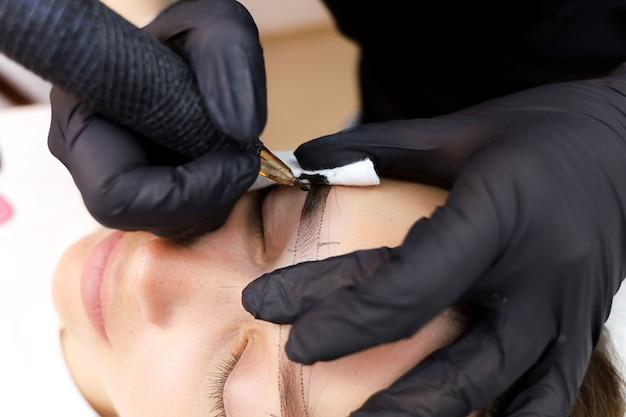 영구 메이크업 아티스트는 손으로 눈썹을 잡고 피부를 펴서 눈썹 문신을합니다.