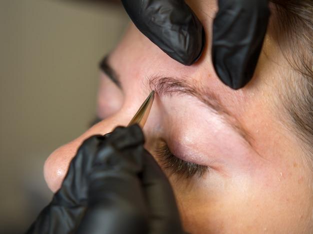 Перманентный макияж. красивая молодая женщина, получающая процедуру коррекции бровей. выщипывание бровей девушки пинцетом