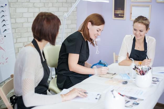 アートメイク教室。対称的な眉毛をスケッチする方法を女性インターンに教える美容師。