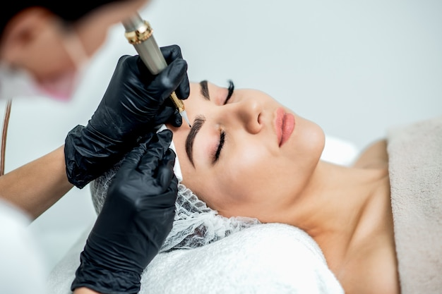 Permanent makeup on eyebrows by professional cosmetologist.