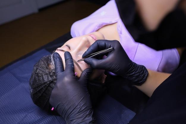 Мастер перманентного макияжа выщипывает лишние волоски на бровях из готовой татуировки.