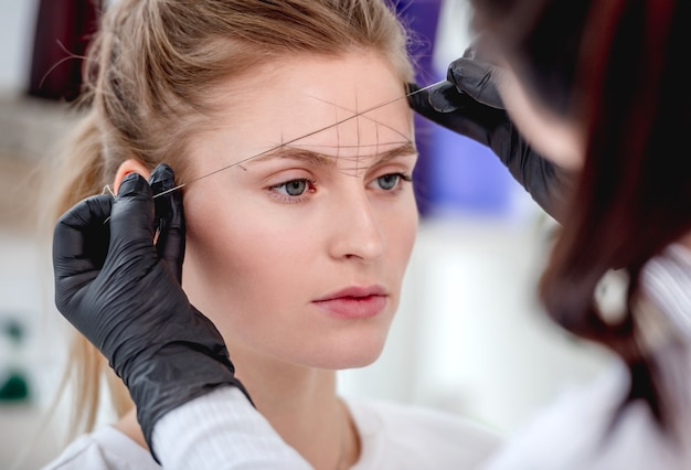 Permanent tattoo makeup master defines the ideal eyebrow shape with professional tools