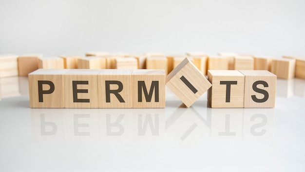Permits text on a wooden blocks, gray background