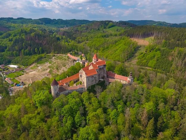 チェコ共和国のボヘミアとモラヴィアの高地の深い森の上の丘の上に立っているモラヴィアの城pernstejnの空撮