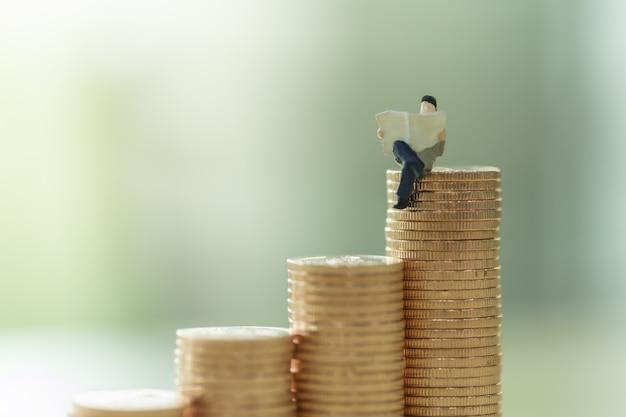 お金、ビジネス、保存、計画のコンセプト。座っていると金貨のスタックで新聞を読んで実業家ミニチュアフィギュアperopleのクローズアップ