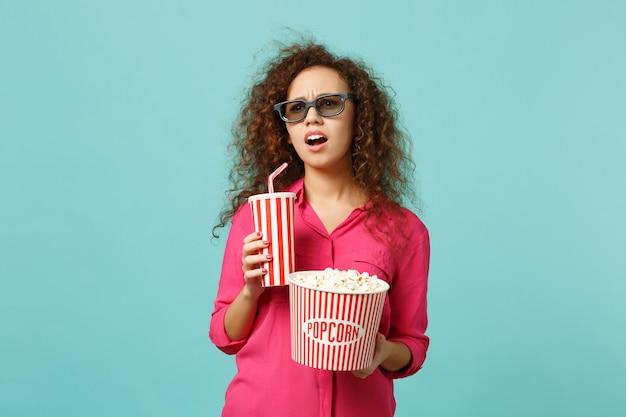 3d 아이맥스 안경을 쓴 어리둥절한 아프리카 소녀가 스튜디오의 파란색 청록색 배경에 격리된 팝콘 음료수 한 컵을 들고 영화 영화를 보고 있습니다. 영화 라이프 스타일 개념에 있는 사람들의 감정. 복사 공간을 비웃습니다.