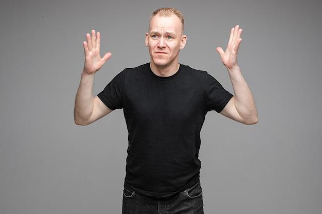 灰色の背景でポーズをとっている間空中で手を上げる黒いシャツの困惑した悲しい男