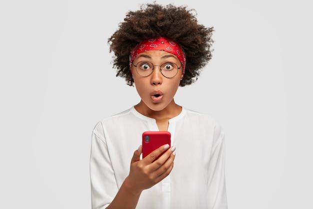 困惑して心配している浅黒い肌の美しい女の子がスマートフォンを持って、驚いた表情で見つめる