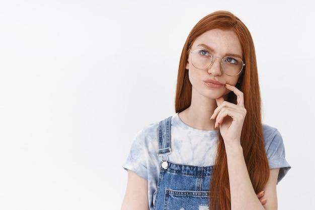 Озадаченная привлекательная молодая рыжая девушка думает о решении головоломки в голове, нахмурилась, прикоснулась к губам, задумчивая, размышляя, решительно подняв голову, сделайте важный выбор, встаньте у белой стены