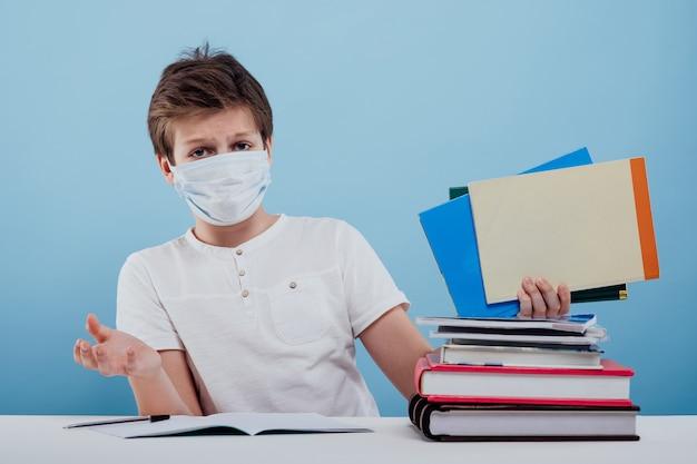 얼굴에 의료용 마스크를 쓴 당황한 소년이 공책과 책을 손에 들고 c를 바라보고 있습니다.