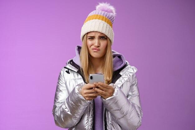 困惑した不機嫌なかわいい金髪のスタイリッシュな女の子は、スマートフォンを持ってしがみつく嫌な眉をひそめている不本意なアンサーメッセージは、不確かな紫色の背景に立って、失望した困惑したテキストを受け取ります。