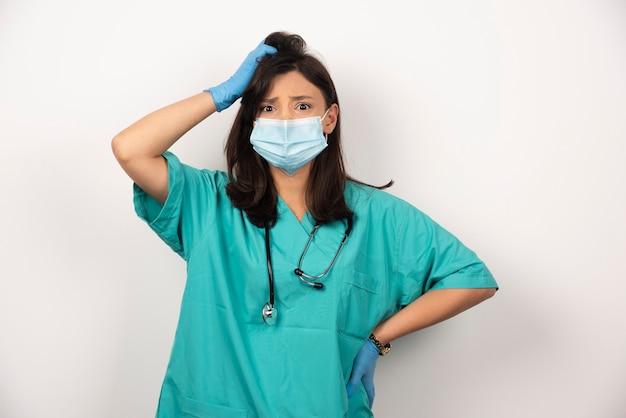 의료 마스크와 장갑 흰색 배경에 생각에 당황한 의사. 고품질 사진