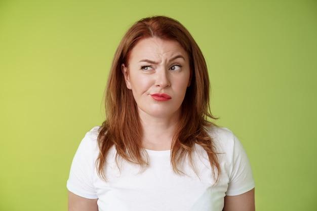 困惑した疑わしい不確かな赤毛の妻が不満を持って眉をひそめているのを見て、不機嫌で失望して躊躇している