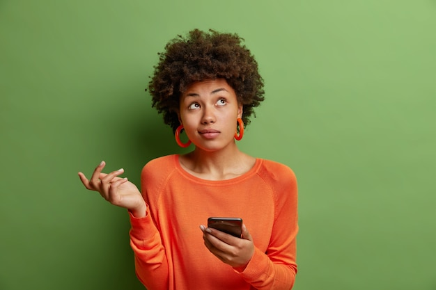 困惑した躊躇する縮れ毛の女性は肩をすくめ、上向きに集中したスマートフォンデバイスを使用しているかどうかわからない緑のスタジオの壁に隔離されたカジュアルなオレンジ色のジャンパーを着ています