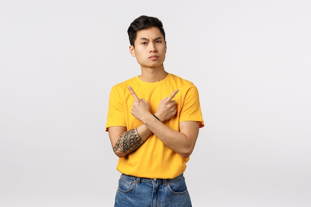 Perplexed and hesitant skeptical asian male customer, facing hard choice, difficult decision during promo, sale offer, pointing sideways with arms crossed over chest, showing left and right variant