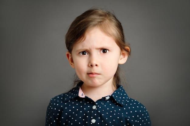 Perplexed little caucasian kid girl 4 6 yo in a blue dress on grey background studio portrait