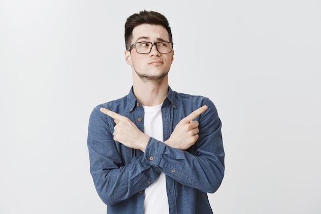 Озадаченный мужчина в очках принимает решение, указывая пальцами в сторону