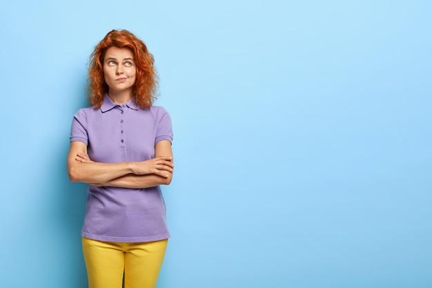 Озадаченная миллениальная женщина с волнистыми рыжими волосами позирует