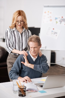 Perplexed puzzled elderly man sitting in the office and demonstrating irritation while working and expressing indignation towards coworker seduction