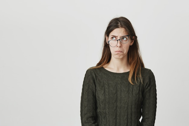 Perplexed and puzzled young woman in crooked glasses looking left troubled