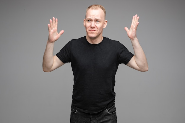 Perplexed and sad man in black shirts raising hands in the air while posing in grey background